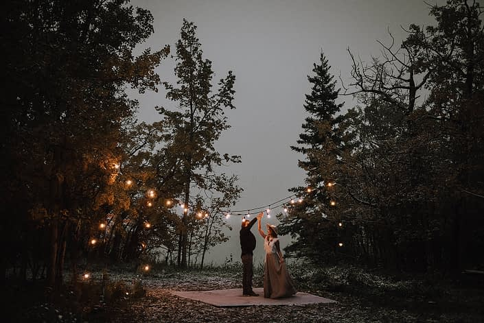 Couple dancing under twinkly lights in the woods