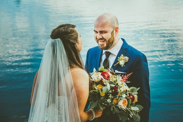 Bride and Groom, Bianca and Matt, with mustard yellow boutonniere and bridal bouquet designed with craspedia, garden roses, golden mustard roses, plum dahlias, white ranunculus, red astilbe, olive branches and eucalyptus.