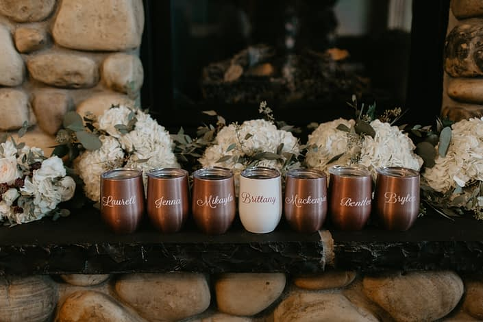 Bridesmaid gift; rose gold wine travel mugs in front of white hydrangea bridesmaid bouquets