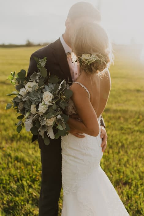 Bride and groom, Leah and Chance; bride hair flowers designed with white spray roses, lisianthus and astilbe with a touch of greenery; bridal bouquet featuring white Playa Blanca roses, white lisianthus, white astilbe, Blue Star succulents, dusty miller and eucalyptus greenery.