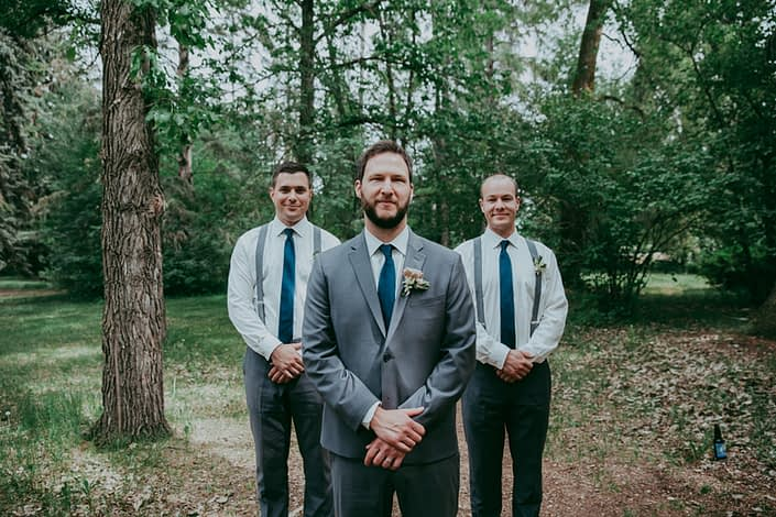 Groom in charcoal suit with navy tie wearing succulent boutonniere with groomsmen in charcoal pants and suspenders with navy ties