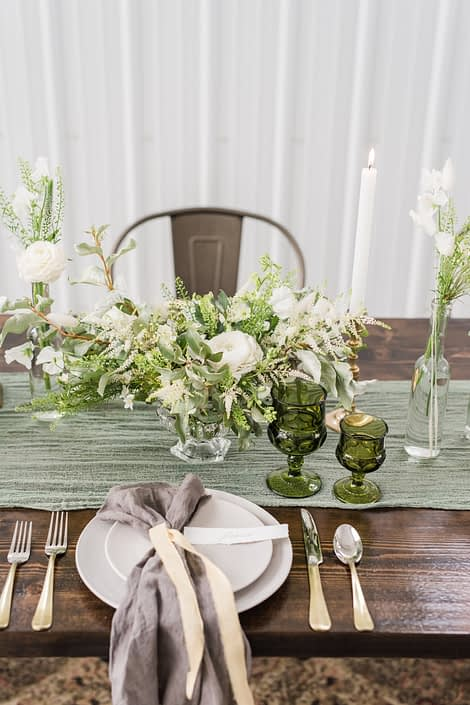 Romantic industrial place setting with vintage green glasses, and a white and green centrepiece featuring white poppies.