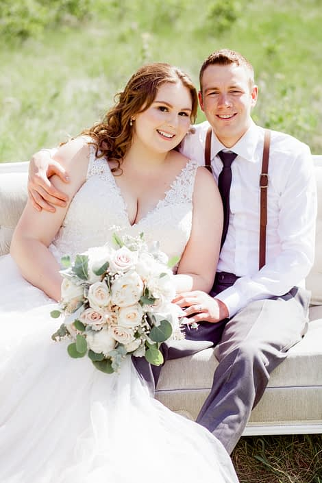 Kuera and Mark on a tufted sofa; Keura is holding a cream and blush bridal bouquet featuring white o'hara garden roses, quicksand roses, white peonies, pale pink astilbe, babies breath, dusty miller and eucalyptus; groom is wearing suspenders.