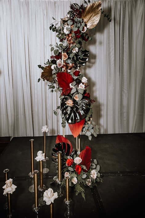 Cambridge Bridal Show 2020 - dramatic tall vertical arrangement made of black monstera leaves, red and metallic dyed Anahaw palm leaves, and blush roses.