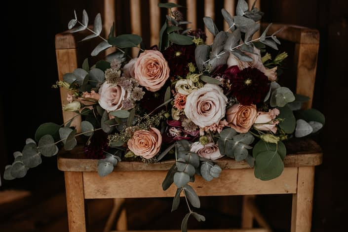 Crystal and Chance's Sweet Haven Barn Wedding - Crystal's bridal bouquet designed with pale pink astrantia, burgundy cymbidium, burgundy dahlias, peach lisianthus, cappuccino roses, quicksand roses and a mixed variety of eucalyptus greenery.