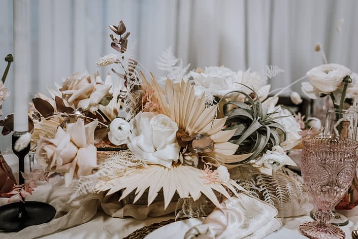 Centrepiece closeup at the With This Ring Bridal Gala 2020 featuring cream coloured dried foliage, white roses, metallic dyed eucalyptus and an air plant.