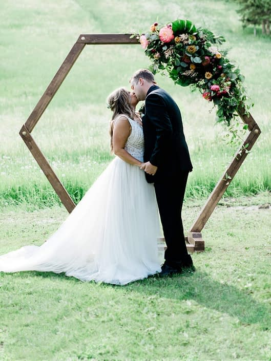 Bride and groom Taylor and Griffin standing under wooden hexagon arch adorned with large arrangement of coral charm peonies, yellow roses, burgundy dahlias, eucalyptus, salal, monstera leaves and plumosa greenery.