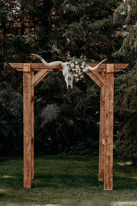 Wooden archway with longhorn skull attached at the centre decorated with quicksand roses, white ranunculus, ivory lisianthus and panda anemones with fresh mixed eucalyptus greenery.