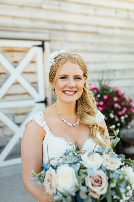 Kelsie holding a blush and blue bridal bouquet designed with succulents, white o'hara garden roses, quicksand roses, blue delphinium, babies breath and a mixed variety of eucalyptus greenery.