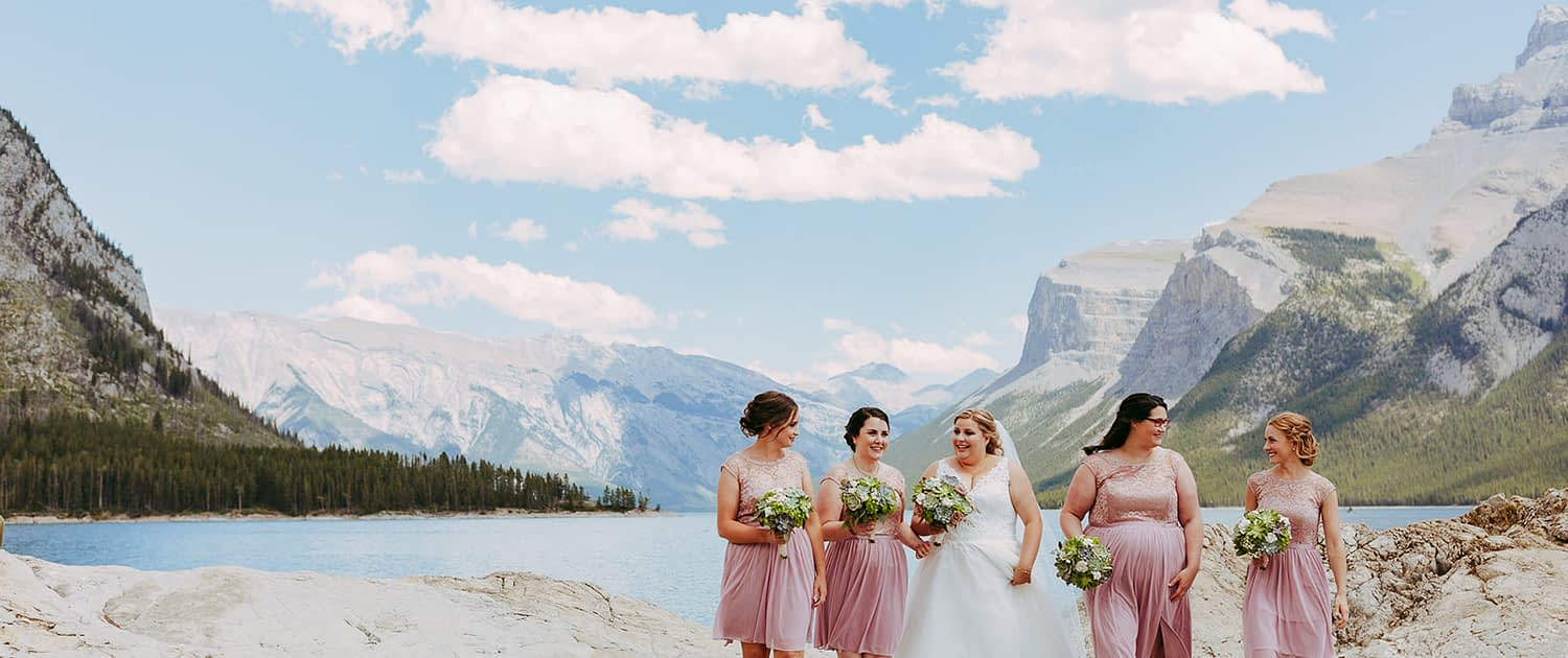 Bride with bridesmaids at a rocky mountain lake holding succulent and paper flower bridal bouqets