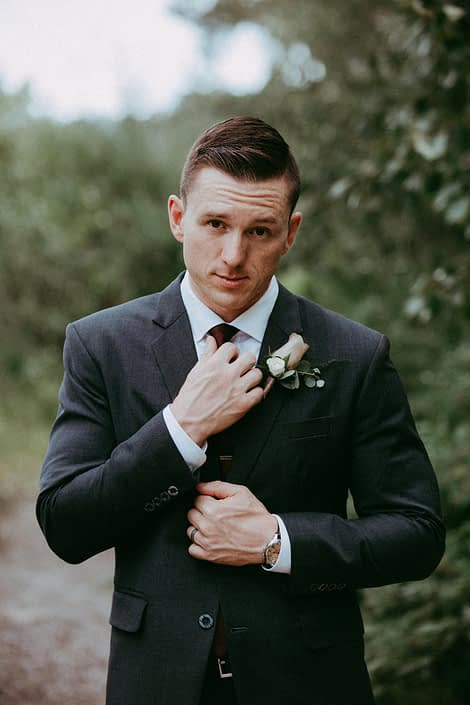 Groom in dark grey suit with mauve rose boutonniere