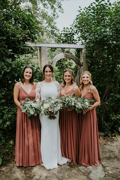 Bride with bridesmaids wearing white and rusty rose dresses, carrying white, ivory and blush bouquets