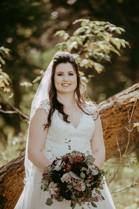 Bride with bridal bouquet designed with pale pink astrantia, burgundy dahlias, brown lisianthus, burgundy ranunculus, quicksand roses and eucalyptus
