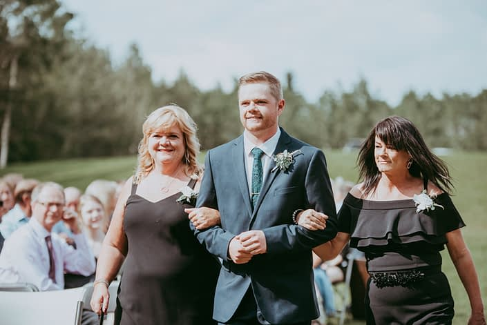 Groom walking mother of bride and mother of groom down the aisle; all wearing pin-on style boutonnieres or corsages