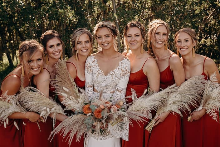 Orange boho - Bride and bridesmaids with bouquets; bridal bouquet designed with orange dahlias, ranunculus, cappuccino roses, bleached bracken fern, bunny tail, eucalyptus, olive branches and pampas grass; bridesmaid bouquets designed with pampas grass, bleached bracken fern and bunny tail