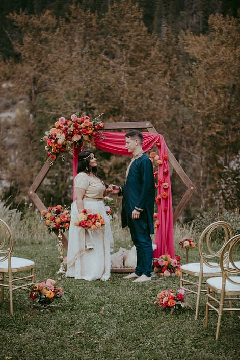 Bride and groom under wooden archway surrounded by colourful and bold flowers