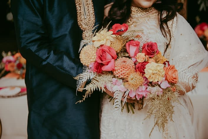 Bold bridal bouquet designed with orange and fuchsia coloured flowers such as roses, zinnias, sweet peas, dahlias, bleached bracken fern and gold painted plumosa