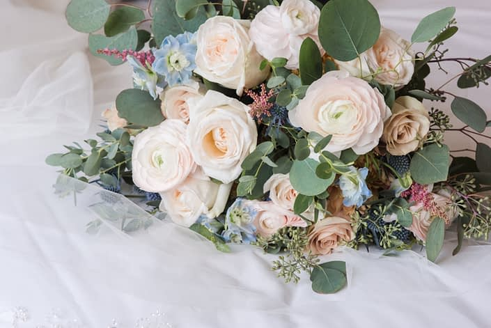 Up close shot of Amy's Pink and Blue bridal bouquet featuring white o'hara garden roses, quicksand roses, blush ranunculus, blue delphinium, eryngium, astilbe and a mixed variety of eucalyptus greenery.
