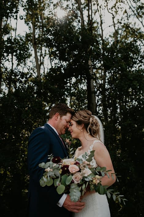 bride and groom with bridal bouquet designed with burgundy dahluas, cappuccino roses, quicksand roses, burgundy cymbidium and astrantia with eucalyptus greenery.