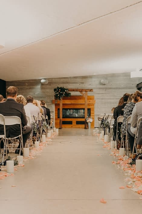 Rustic wedding with rose petals and candles down the aisle and a corner arch piece with red and blush roses