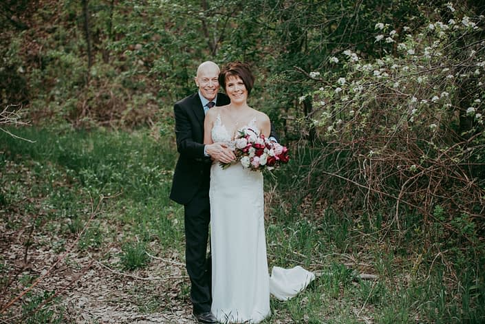 Bride and groom, Sandra and David, embracing and holding an elegant pink and burgundy bouquet designed with Sarah Bernhardt peonies, Helleborus, Ranunculus, Black Bacarra roses, Blackberry Scoop Scabiosa, Burgundy Tulips, Pale Pink Astrantia and eucalyptus.