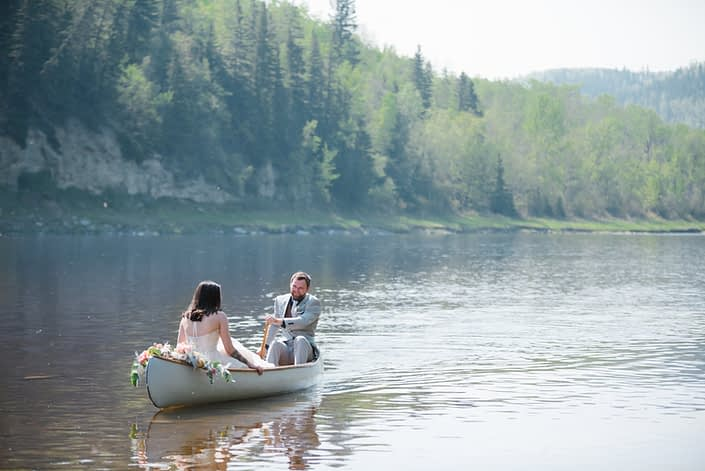 Bride and groom in a canoe on the river. The canoe is adorned with a blush and coral bouquet.