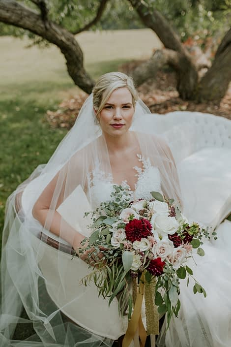 bride sitting on an antique ivory sofa holding a bridal bouquet designed with ivory, blush and burgundy and trailing gold sequin ribbons wearing a cathedral length veil