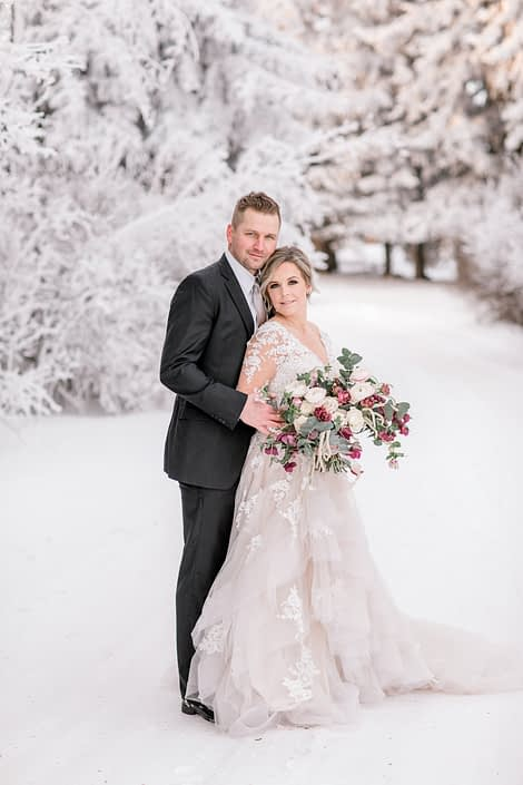 Bride and groom with blush and burgundy bouquet in the snowy winter