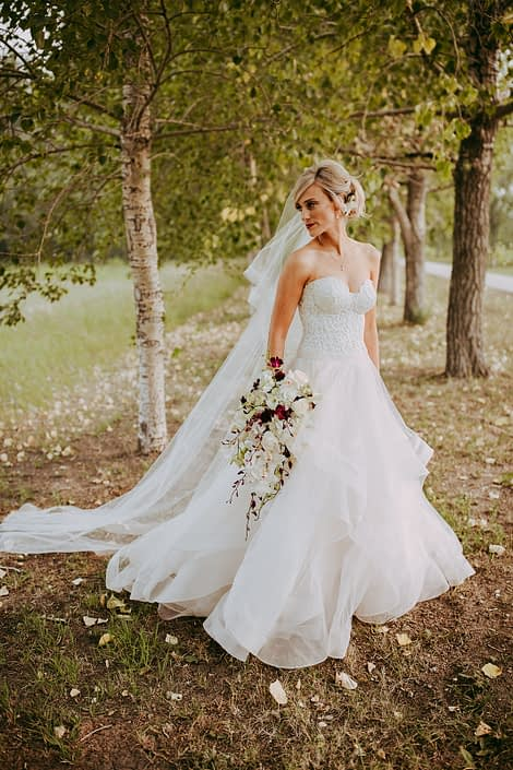 Bride in the trees in a summer wedding wearing a veil and holding a cascade bridal bouquet designed with dendrobium orchids and cymbidium orchids in white and burgundy and white calla lilies