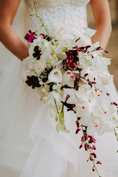 bride holding a cascade bouquet designed with white calla lilies, burgundy orchids and white cymbidium orchids