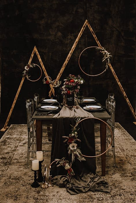 Alternative wedding decor dark and moody black backdrop with triangle arches and copper floral hoops ad grey velvet table runner on a wood table with acrylic chairs and red ranunculus and white anemone and black chargers
