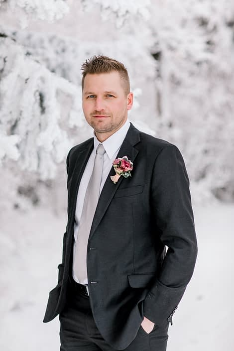 Winter groom standing in snow wearing blush and burgundy boutonniere