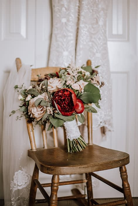 Bride's bouquet, veil and dress with a vintage rustic wooden chair. Bouquet features red charm peony, quicksand roses, burgundy astrantia, pale pink astilbe, and blush spray roses. It was finished with eucalyptus greenery and a blush satin with lace overlay wrapped handle.