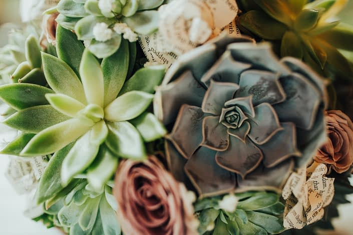 Close up photo of succulent bridal bouquet with tucks of mauve amnesia roses and book paper flowers