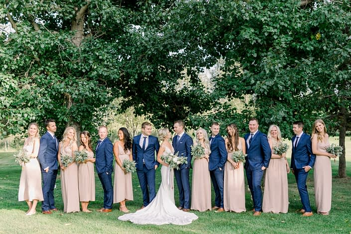 Timeless white wedding bridal party; bride wearing white lace bridal gown and holding a blush and white bouquet; bridesmaids wearing blush floor-length gowns and holding simple white astilbe and greenery bouquets; groom and groomsmen wearing navy suits.