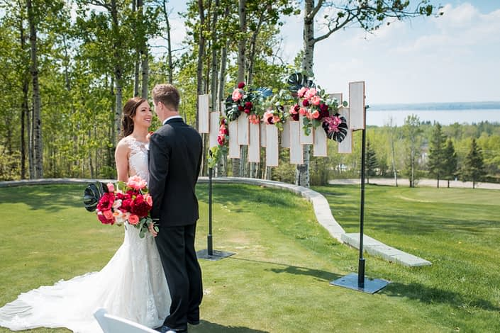 bride and groom with coral and burgundy bridal bouquet and archway geometric backdrop in coral peonies and black monstera