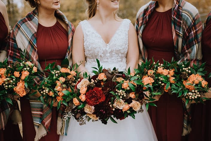 Rustic fall wedding bride and bridesmaids with orange, red, burgundy and yellow bouquets featuring roses, hypericum berries and dahlias.