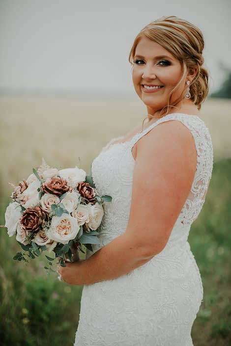 Bride in a summer wheat field with wedding dress and bridal bouquet of rose gold succulents and ivory garden roses and blush roses and eucalyptus