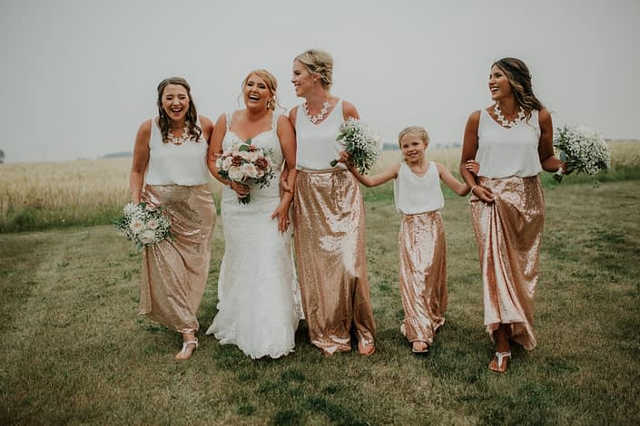 bride with bouquet of rose gold succulents and ivory garden roses and blush quicksand roses and bridesmaids in sequin rose gld skirts holding bouquets of babies breath and garden roses