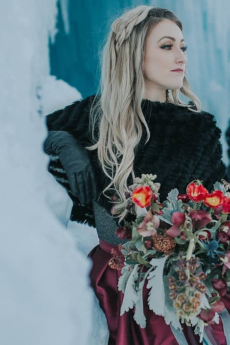Engagement photos in winter at the ice castles with a bridal bouquet of dusty milller, red tulips and burgundy frittilaria