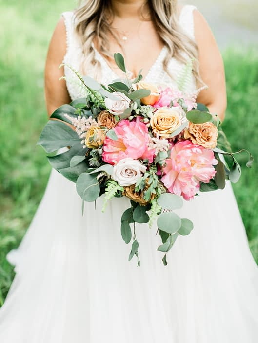 Modern Coral Charm Peony bouquet accented with golden mustard roses, quicksand roses, cappuccino roses, astilbe, astrantia, monstera leaf, boston fern and eucalyptus greenery.