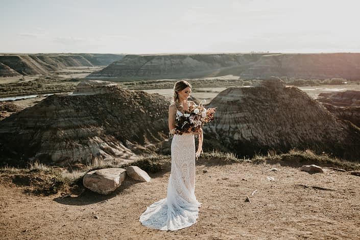 bride in the drumheller badlands in a lace dress holding an organic boho styled bridal bouquet