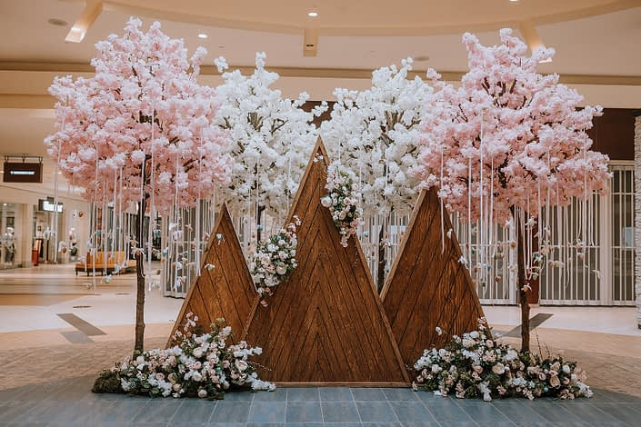 Wooden mountains backdrop decorated with artificial botanicals and Easter Eggs for the Bower Place Easter 2021 Display.