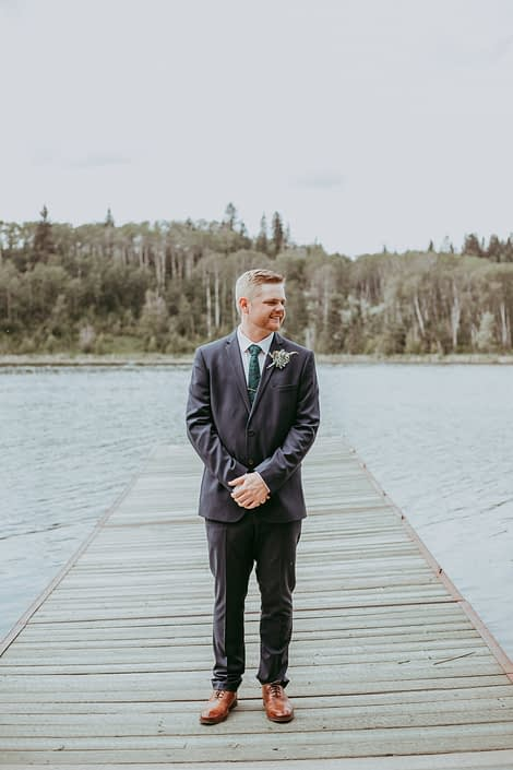 Groom on a dock with a succulent boutonniere accented by astilbe, gold scabiosa pod and greenery