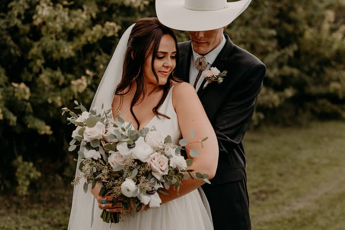 Colt and Erika embracing - colt is wearing a blush and white boutonniere made with spray roses and eucalyptus. Erika is holding a blush and white bridal bouquet featuring quicksand roses, ivory ranunculus, panda anemones, lisianthus and a variety of eucalyptus greenery.