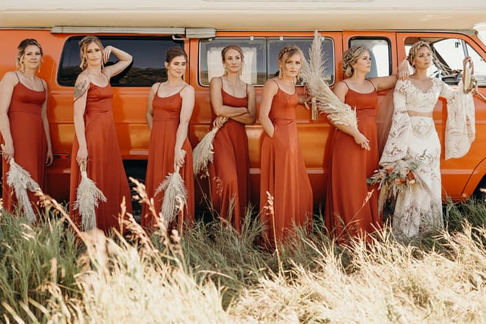 Bridesmaids wearing orange dresses with pampas grass bouquets and boho bride