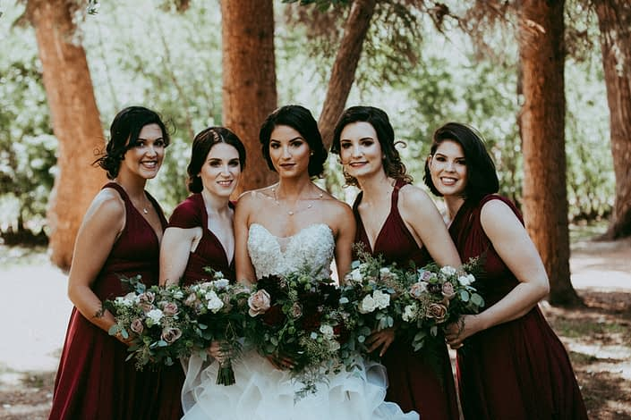 Bride and bridesmaids; wearing burgundy dresses and carrying bouquets designed with dahlias, garden roses, roses, lisianthus, plumosa and eucalyptus