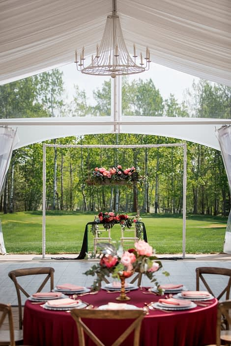 Clearspan wedding tent with chandelier and sweetheart table and wedding table in burgundy, black and coral