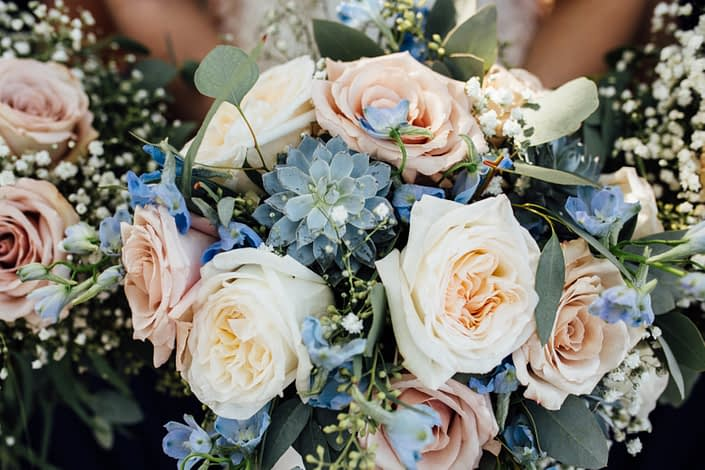 Blush and blue bridal bouquet featuring quicksand roses, white o'hara garden roses, succulents, blue delphiniums, babies breath (gypsophila), and a mixed variety of eucalyptus greenery (feather, gunni, silver dollar and seeded)