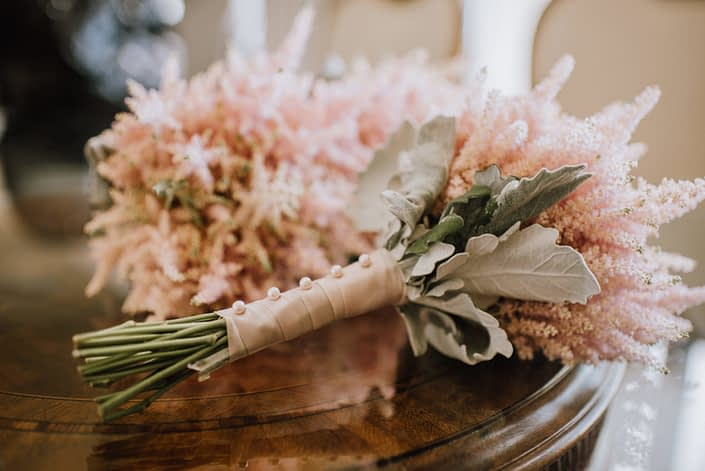 bridesmaid bouquets designed with pale pink astilbe and dusty miller wrapped wtih blush satin ribbon and pearl pins